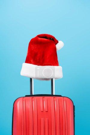 Photo pour Chapeau santa rouge sur sac de voyage moderne isolé sur bleu - image libre de droit