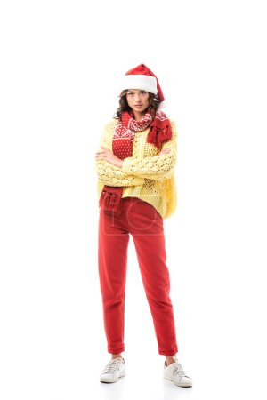 Photo for Young brunette woman in santa hat and red scarf standing with crossed arms isolated on white - Royalty Free Image