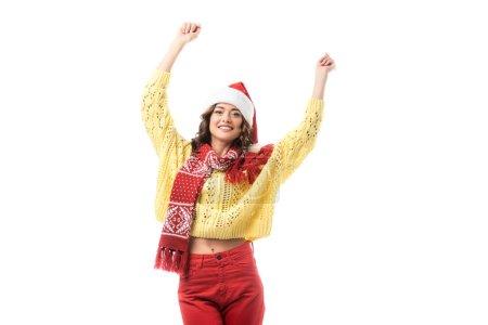 junge glückliche Frau mit Weihnachtsmütze und rotem Schal, die Hände über dem Kopf isoliert auf weißem Grund stehend