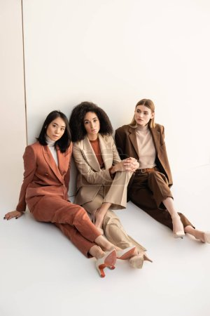 young multicultural women in trendy suits sitting and posing on white