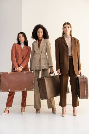 full length of multicultural women in trendy suits holding suitcases on white