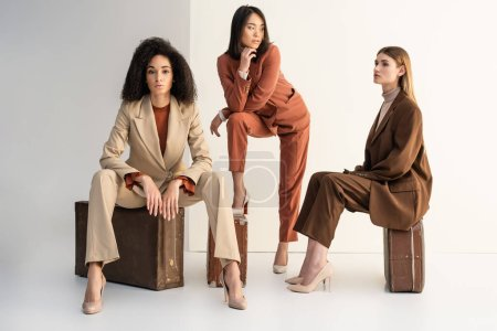 Photo pour Pleine longueur de femmes multiculturelles en costumes à la mode assis sur les bagages sur blanc - image libre de droit