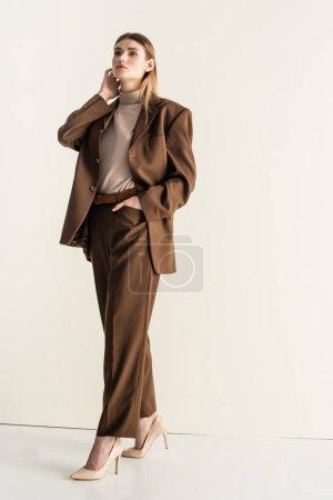 pleine longueur de femme blonde en costume marron élégant regardant la caméra tout en se tenant avec la main dans la poche sur blanc