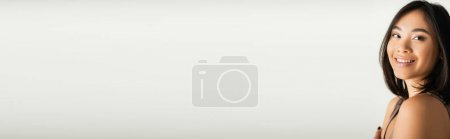 Photo for Brunette asian woman smiling while looking at camera on white, banner - Royalty Free Image
