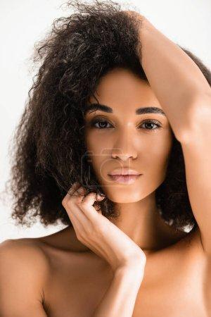 Mujer afroamericana mirando a la cámara mientras posa aislada en blanco