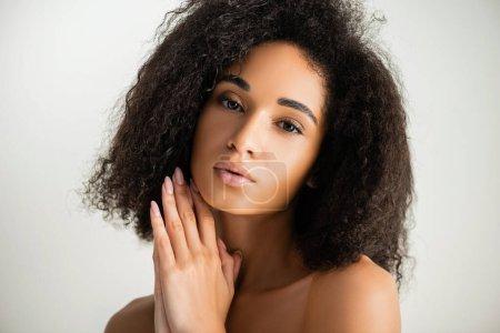 Afroamerikanerin blickt isoliert auf weiße Kamera