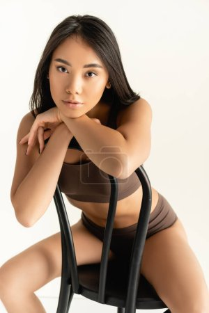 Photo for Brunette asian woman in beige underwear looking at camera while posing on chair isolated on white - Royalty Free Image