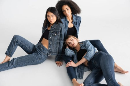 high angle view of young interracial women in denim outfit posing on white