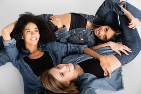 top view of cheerful young interracial women in denim shirts posing isolated on white