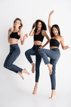 Photo for Excited interracial women in denim jeans jumping and posing on white - Royalty Free Image