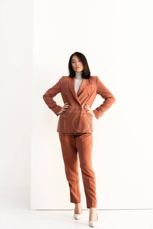 full length of brunette asian woman in trendy suit standing with hands on hips on white