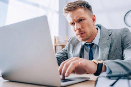 Konzentrierter Geschäftsmann mit Laptop im Büro