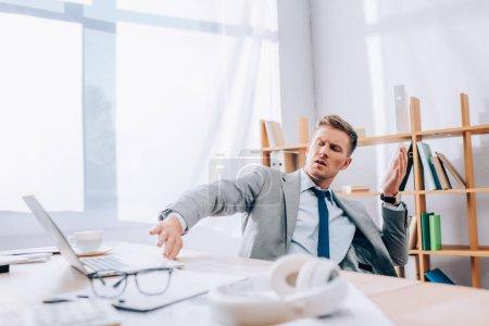 Photo pour Homme d'affaires gêné repoussant ordinateur portable près des écouteurs et des lunettes sur le premier plan flou dans le bureau - image libre de droit