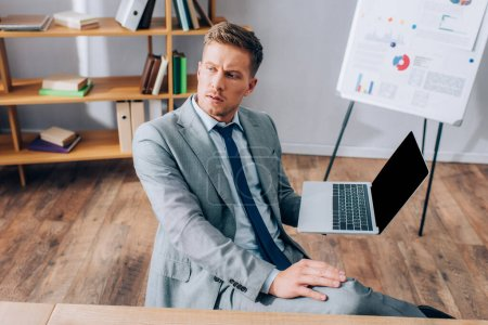 Young businessman in suit holding laptop with blank screen in office