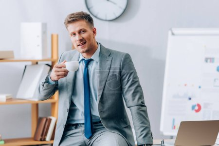 Photo for Smiling businessman holding cup of coffee near laptop - Royalty Free Image