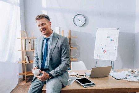 Fröhlicher Geschäftsmann mit Kaffeetasse in der Nähe von Geräten und Papieren im Büro