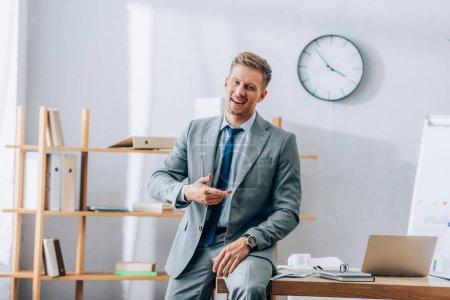 Alegre hombre de negocios sonriendo mientras está sentado cerca de dispositivos unas gafas en la mesa de trabajo