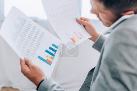 Papers with graphs in hands of businessman talking on smartphone on blurred foreground