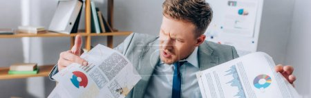 Irradiated businessman holding dirty papers in office, banner