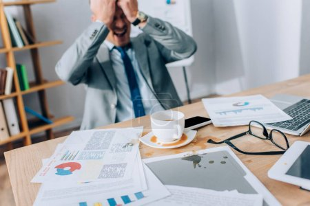 Photo for Pouring out coffee near papers, devices and screaming businessman on blurred background - Royalty Free Image
