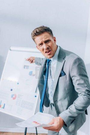 Photo pour Homme d'affaires en colère regardant la caméra tout en pointant vers le tableau à feuilles avec des graphiques sur fond flou dans le bureau - image libre de droit