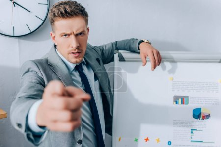 Serious businessman pointing with finger at camera on blurred foreground near flipchart with graphs