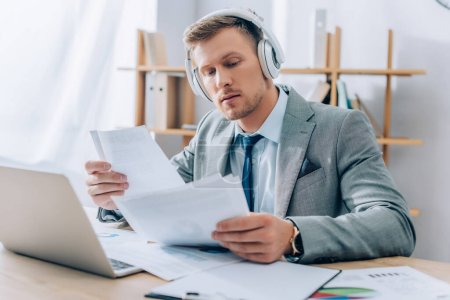 Young businessman listening music in headphones while working with papers near laptop on blurred foreground
