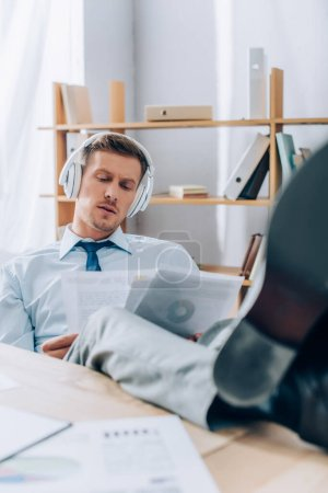 Businessman in headphones working with papers while putting legs on table on blurred foreground