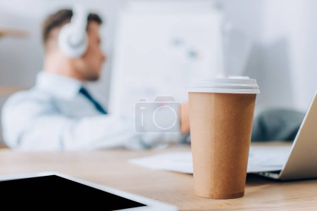 Photo for Digital tablet and coffee to go on table near businessman working on blurred background - Royalty Free Image