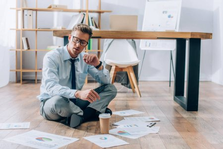 Businessman sitting on floor near coffee to go and papers in office