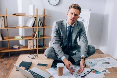 Verwirrter Geschäftsmann blickt auf Kamera in der Nähe von Geräten und Papieren auf Tisch