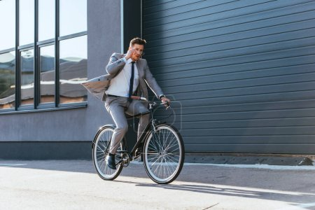 Photo for Businessman in suit holding eyeglasses while cycling near building - Royalty Free Image