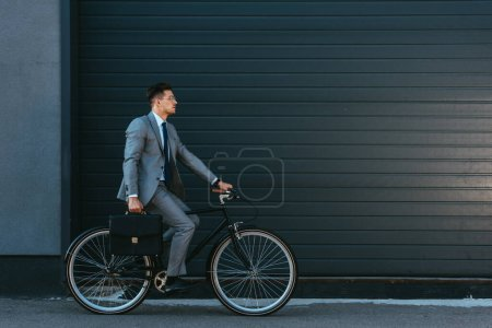 Photo for Young businessman with briefcase cycling near facade of building - Royalty Free Image