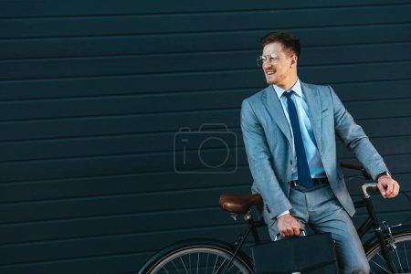 Photo pour Homme d'affaires souriant tenant une mallette près du vélo et du bâtiment - image libre de droit