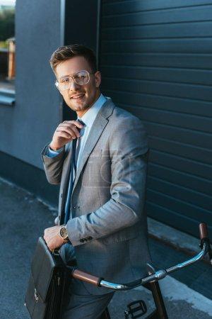 Lächelnder Geschäftsmann mit Aktentasche und Krawatte im Freien