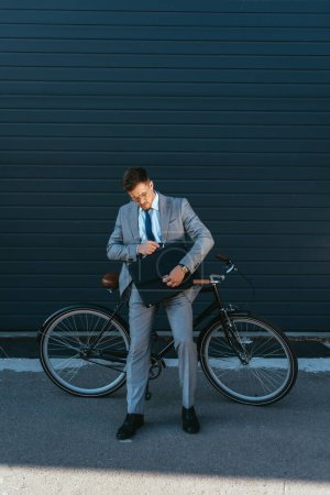 Businessman with briefcase standing near bike outdoors
