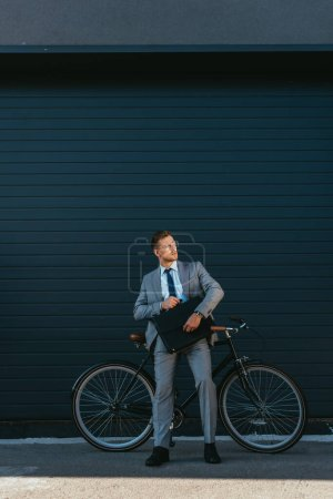 Photo for Young businessman holding briefcase while standing near bike and building - Royalty Free Image