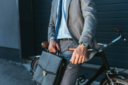 Cropped view of businessman in suit holding briefcase near bicycle outdoors