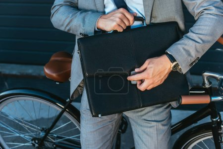 Cropped view of businessman locking briefcase beside bicycle outdoors