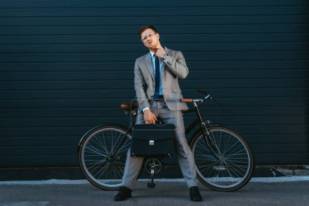 Young businessman with briefcase looking at camera near bike outdoors