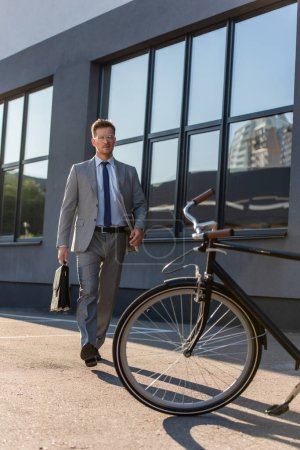 Photo for Businessman with briefcase walking to bicycle outdoors - Royalty Free Image