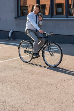 Young businessman holding jacket while cycling outdoors