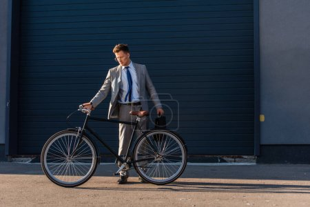 Photo for Businessman in formal wear holding briefcase near bicycle and building outdoors - Royalty Free Image
