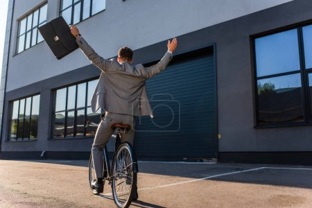 Photo for Back view of businessman with raised hands holding briefcase while riding bicycle outdoors - Royalty Free Image