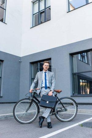 Photo pour Homme d'affaires en lunettes et costume tenant la mallette près du vélo et du bâtiment - image libre de droit