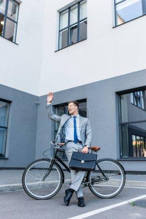 Photo pour Homme d'affaires joyeux agitant la main tout en tenant la mallette près de vélo à l'extérieur - image libre de droit