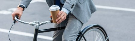 Photo for Cropped view of businessman holding coffee to go while cycling outdoors, banner - Royalty Free Image