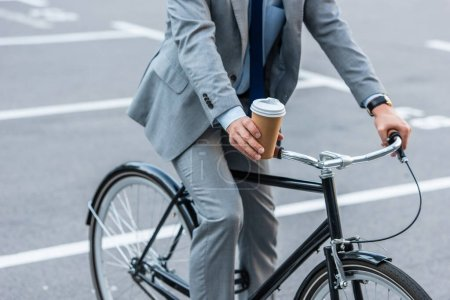 Cropped view of businessman holding takeaway coffee while riding bicycle outdoors