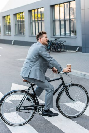 Smiling businessman with coffee to go riding bicycle on crosswalk outdoors