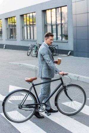 Photo pour Vue latérale de l'homme d'affaires tenant café à emporter près de vélo sur le passage supérieur à l'extérieur - image libre de droit